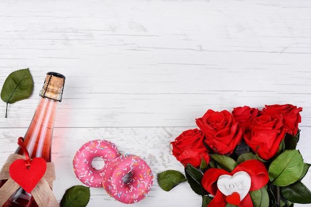 Rose cornice, bottiglia di champagne, cuore decorativo, ciambelle, nastro rustico, sulla superficie in legno.