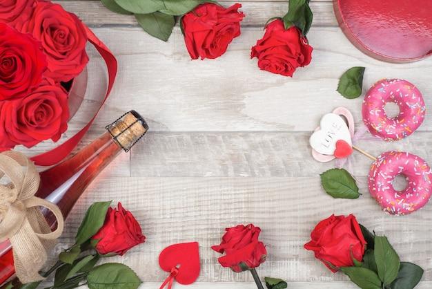 Rose cornice, bottiglia di champagne, ciambelle, cuore decorativo, nastro rustico, sulla superficie in legno.