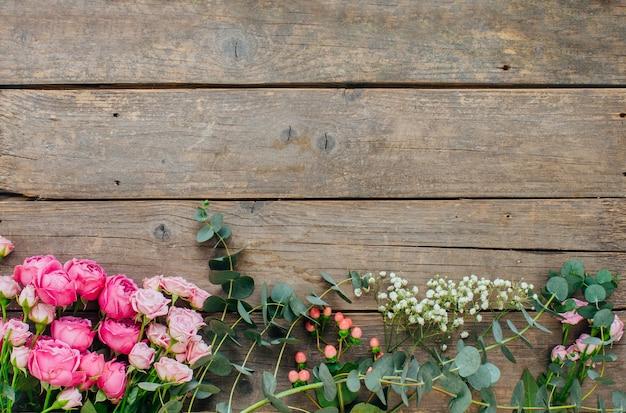 Cornice di rose, eucalipto, eustoma, fiori di gypsophila su fondo di legno del mestiere con spazio vuoto per testo. vista dall'alto, piatto.