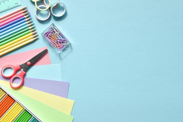 Una cornice di materiale scolastico in colori pastello su sfondo azzurro, spazio per il testo. forniture per ufficio. di nuovo a scuola. era piatto.