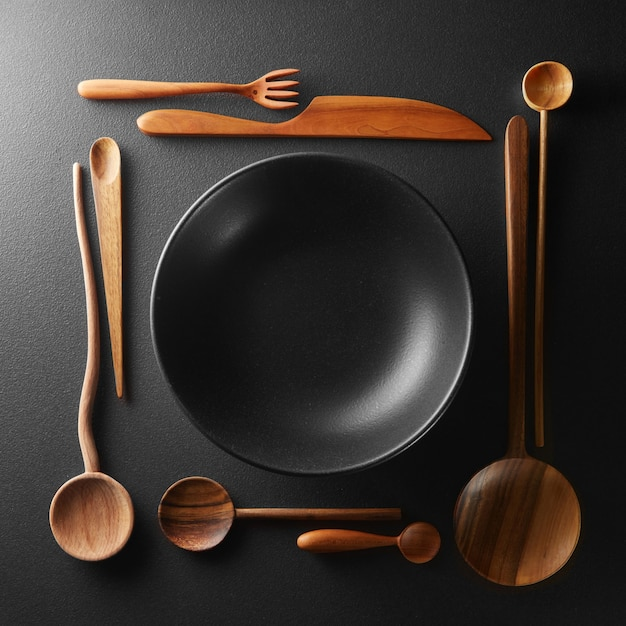 Cornice di impostazione piatto nero vuoto e cucchiaio di legno, forchetta, coltello su un tavolo nero.