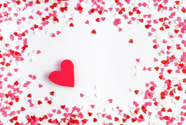 Cornice di piccoli cuori e un grande cuore su sfondo chiaro. vista dall'alto, con spazio per copiare. san valentino