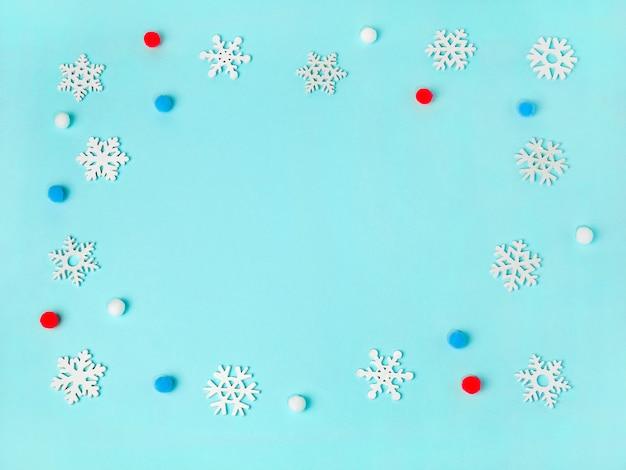 Cornice di fiocchi di neve su sfondo azzurro colori pastello vacanze di natale composizione