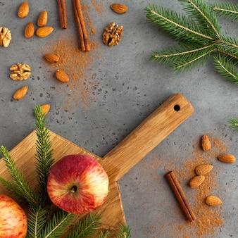 Cornice di rami di abete rosso, cannella, mele e noci. biglietto natalizio. nuovo anno..