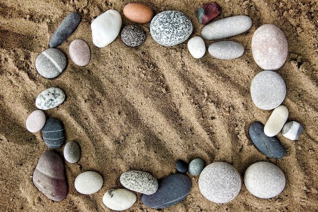 Cornice di pietre su uno sfondo di sabbia closeup. spiaggia. copia spazio