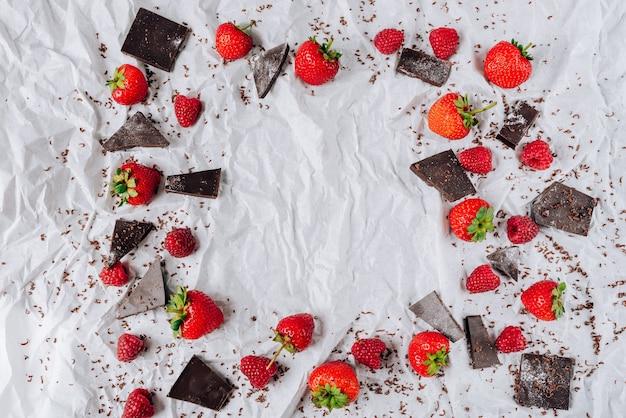 Cornice di fragole e lamponi e cioccolato amaro con uno sfondo di carta alla menta