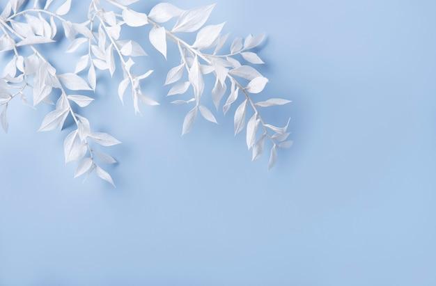 Cornice di rami bianchi con foglie su sfondo blu