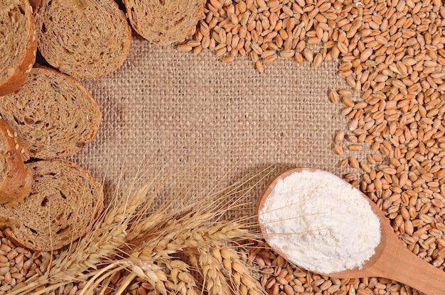 Cornice di farina bianca, grano e pane su uno sfondo di saccheggio