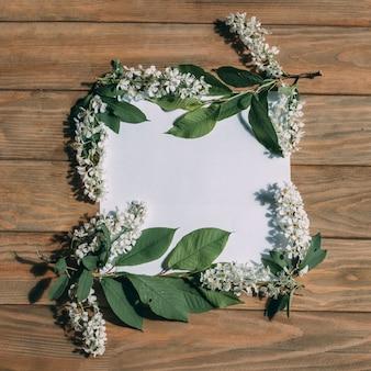 Cornice di fiori bianchi e foglie su uno sfondo di legno con un centesimo isolato bianco