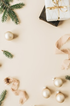 Cornice con spazio vuoto della copia fatto di rami di aghi di abete, scatole regalo, nastri e palline di natale sulla superficie beige