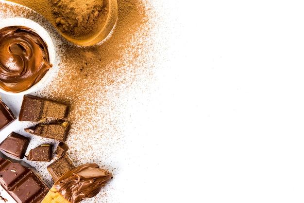 Cornice con diversi tipi di cioccolato, polvere, crema e barretta su sfondo bianco