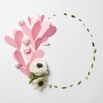 Cornice con cuori, meringa e fiori con copyspace su sfondo bianco