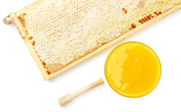 Cornice con nido d'ape, piatto con miele e bastone di miele da vicino su sfondo bianco, isolato. vista dall'alto