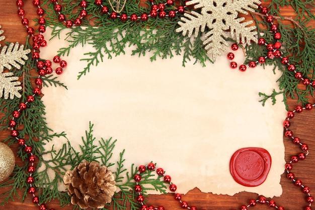 Cornice con carta vintage e decorazioni natalizie su fondo in legno