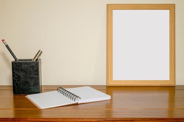 Cornice con schermo bianco su tavolo con taccuino e portapenne e matita