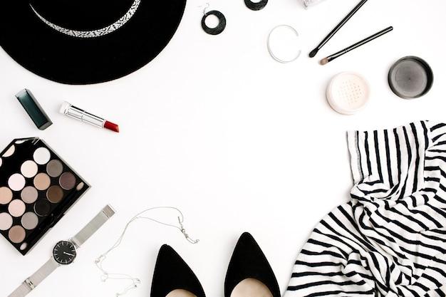 Cornice di vestiti, accessori e cosmetici moderni di moda donna. t-shirt, cappello, scarpe, tavolozza, rossetto, orologi, cipria su bianco