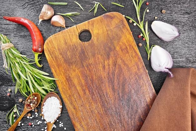 Cornice di aneto di legno, cucchiai con piselli di pepe e sale, rametti di rosmarino fresco, baccelli di peperoncino rosso