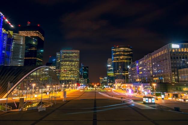 Francia. parigi. quartiere notturno la defense. grande piazza pedonale circondata da moderni grattacieli