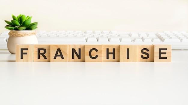 Parola di franchising realizzata con blocchi di legno. concetti di vista frontale, pianta verde in un vaso di fiori e tastiera bianca sullo sfondo