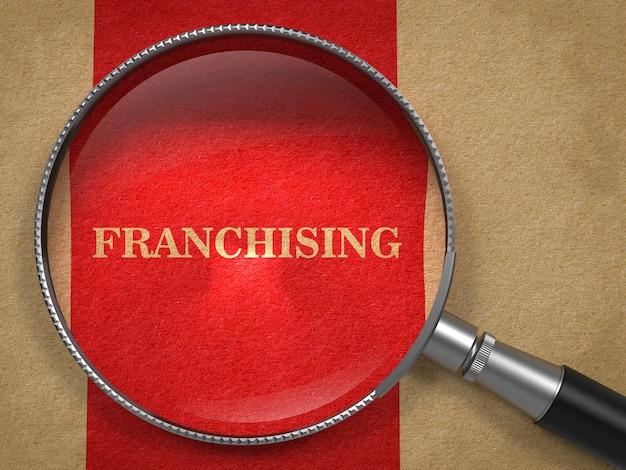 Concetto di franchising. lente d'ingrandimento su carta vecchia con sfondo rosso linea verticale.