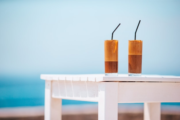 Frappe, caffè freddo sulla spiaggia. frappuccino, frappé o latte ghiacciato del caffè in uno sfondo di vetro alto il mare nel bar della spiaggia