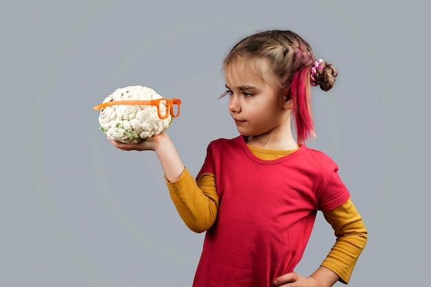Il ragazzino bizzarro detiene frutta e verdura di colore sbagliato deforme, concetto di cibo di scarto