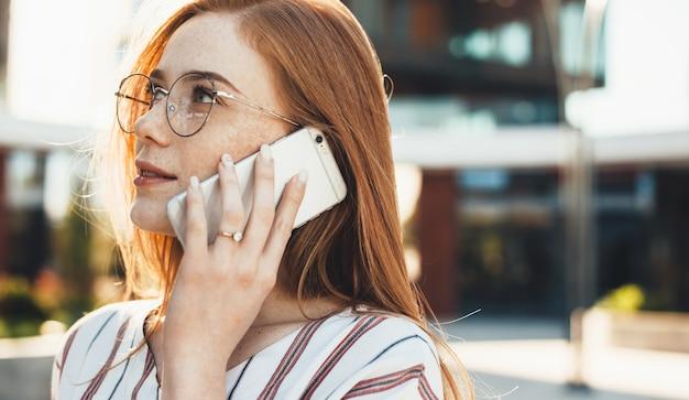 Imprenditore caucasico lentigginoso con capelli rossi e occhiali da vista sta discutendo al telefono all'esterno