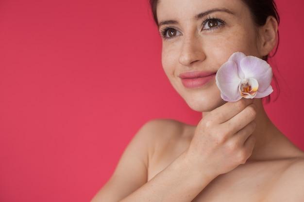 Donna caucasica lentigginosa in posa con un fiore di orchidea vicino alla sua guancia e sorriso su una parete rosa con spazio libero