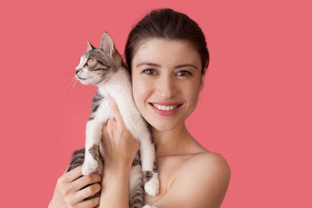 Donna caucasica lentigginosa con spalle nude in posa su un muro rosa con un gatto che sorride davanti