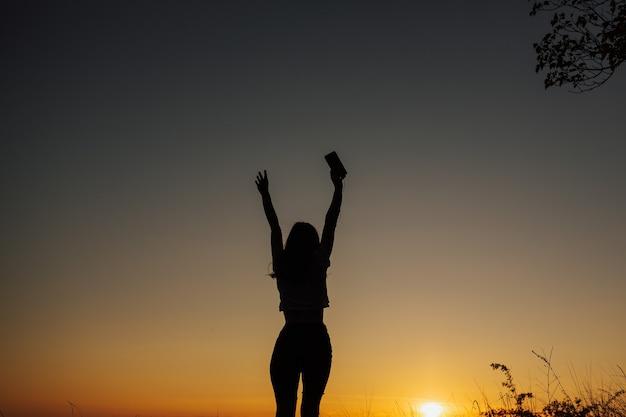Ragazza libera in cuffia ascolta musica e balla con le mani in alto al bellissimo tramonto nel campo.