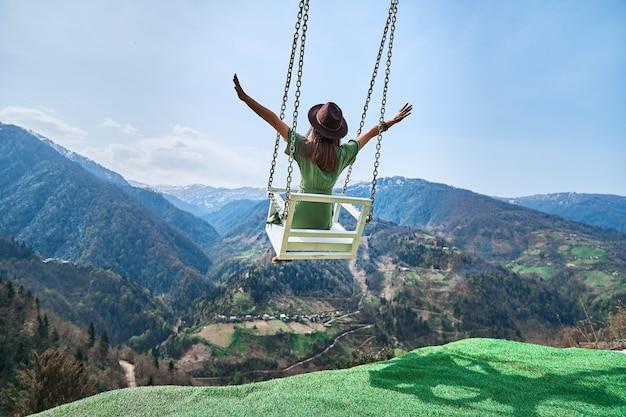 Donna felice e gioiosa viaggiatrice libera con le braccia aperte che oscillano sull'altalena a catena in montagna, godendo di una bella vista e di un bel momento di vita