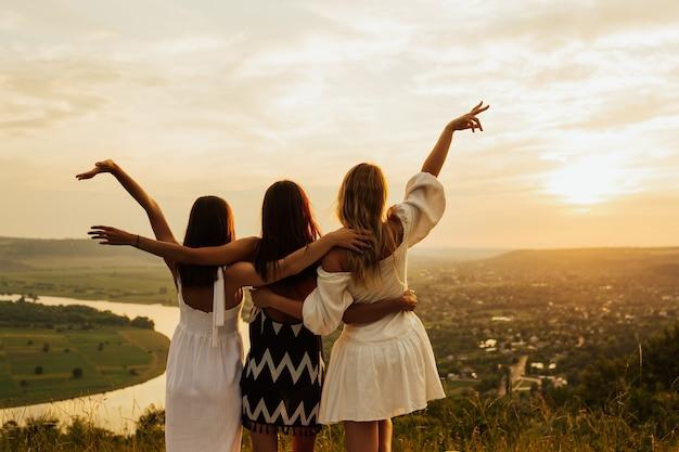 Donne felici libere che godono di un paesaggio fantastico con un bellissimo tramonto.