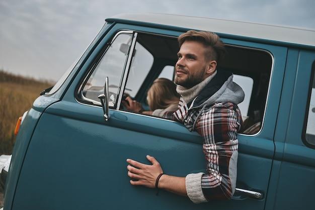 Libero e selvaggio. bel giovane che si sporge dal finestrino del furgone e sorride mentre è seduto sui sedili del passeggero anteriore insieme alla fidanzata