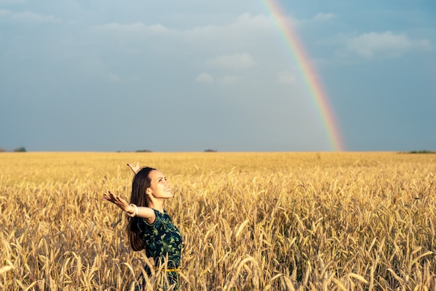 Donna libera in un campo con spighe di grano dorato con le mani aperte a guardare il tramonto su uno sfondo arcobaleno