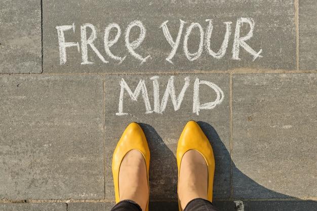 Libera il testo della tua mente sul marciapiede grigio con le gambe della donna, vista dall'alto