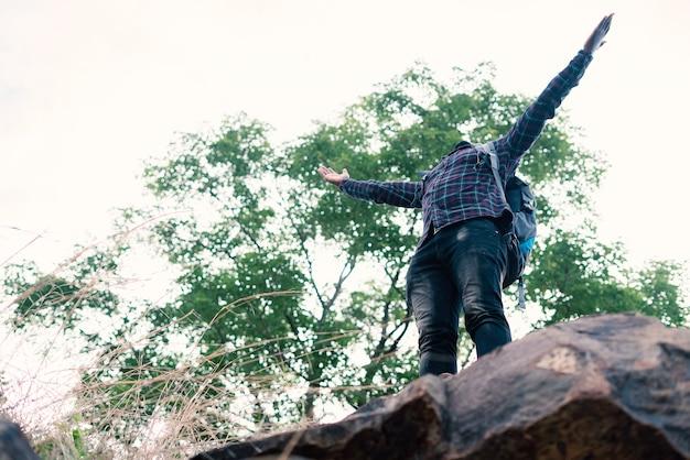 Viaggiatore africano dell'uomo di libertà che sta sulla cima della scogliera e con lo zaino