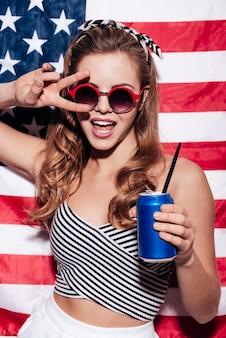 La libertà è nelle sue vene. bella giovane donna che dà pace e tiene in mano una lattina mentre si trova contro la bandiera nazionale americana american
