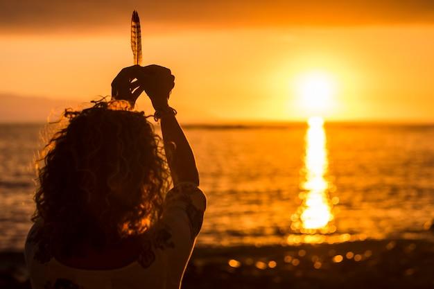 Immagine del concetto di libertà e meditazione con la donna che prende una piuma come la vita durante un bellissimo tramonto colorato di arancione e oro sul mare. bel posto turistico e di vacanza con colori caldi e amore