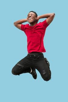 Libertà di movimento e di avanzamento. il giovane africano sorpreso felice che salta un contro il fondo blu dello studio. runnin uomo in movimento o movimento. emozioni umane ed espressioni facciali