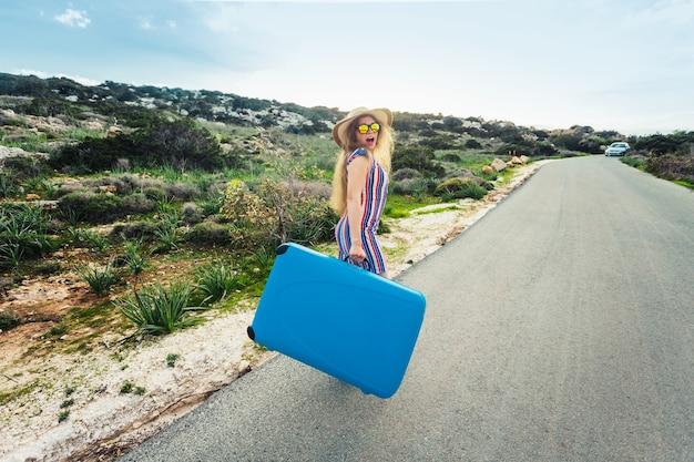 Libertà, viaggio, vacanza e concetto estivo - donna viaggiatrice che cammina per strada con valigie e risate