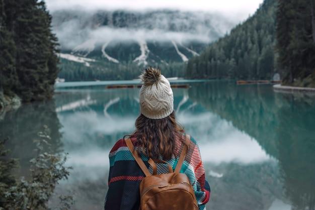 Libertà di viaggio escursionista donna nel lago di braies circondato da montagne dolomitiche, italia. escursioni, viaggi e avventure.