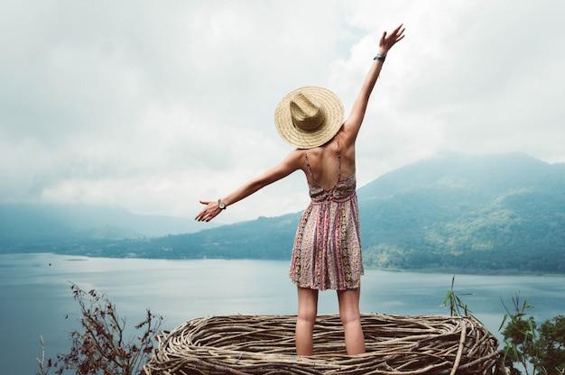 Giovane donna di libertà spensierata e soddisfatta a braccia aperte sul fondo del paesaggio della montagna