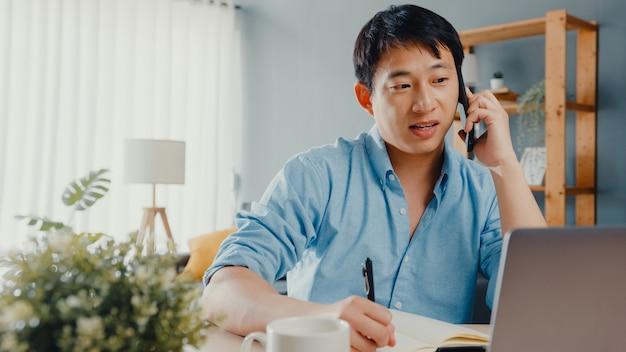 Abbigliamento casual freelance asia guy utilizzando laptop parlare sul telefono cellulare in salotto a casa.