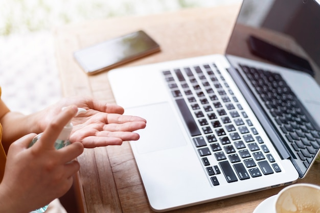 Donna d'affari freelance utilizzando mano mettere disinfettante a portata di mano per la pulizia della mano per prevenire virus e lavorare con il laptop
