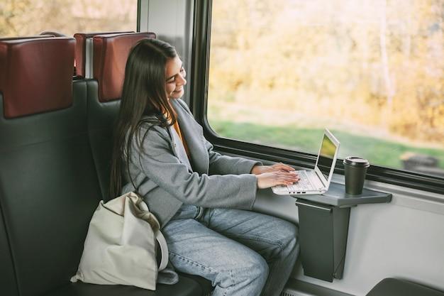 Ragazza freelance seduta su un treno con un computer portatile. tecnologia moderna e networking.