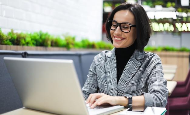Il paradiso dei freelance. foto ravvicinata di una ragazza impegnata in abiti eleganti che digita su un laptop mentre è seduta in uno spazio pubblico.