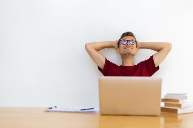 Uomo freelance che lavora da casa nella moderna stanza bianca con computer portatile. nuovo normale, nomade digitale, stile di vita moderno e concetto di business