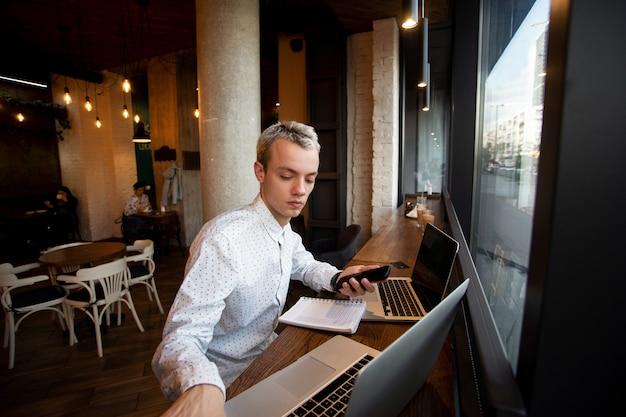 Il programmatore freelance si siede vicino alla finestra in una caffetteria e lavora