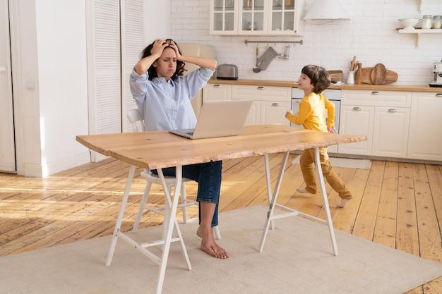 Donna lavoratrice indipendente stanca del figlio rumoroso seduto con il suo computer portatile sul tavolo della cucina
