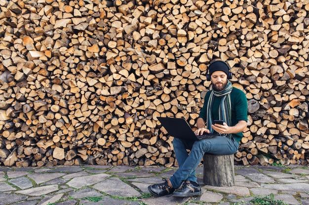 Imprenditore barbuto libero professionista in cuffie che lavorano al computer portatile e utilizza il telefono sullo sfondo del muro di legna da ardere.